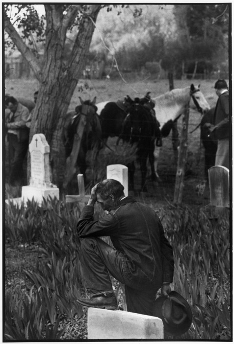 USA. New Mexico. Taos. 1947. The death of a land-owner. His body was taken out to the burial ground in a shiny black motor hearse. Members of the family rode in a stage-coach; cowhands and ranch help came on horseback. During the funeral, this old cowboy bowed his head at the graveside.