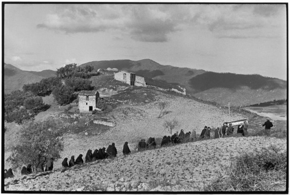 ITALY. Basilicata. Accettura. 1951. A peasant funeral. According to custom, the priest who officiates at the entire ceremony leaves the group halfway to the burial ground. Only the bearers and mourners accompany the body up the hillside.